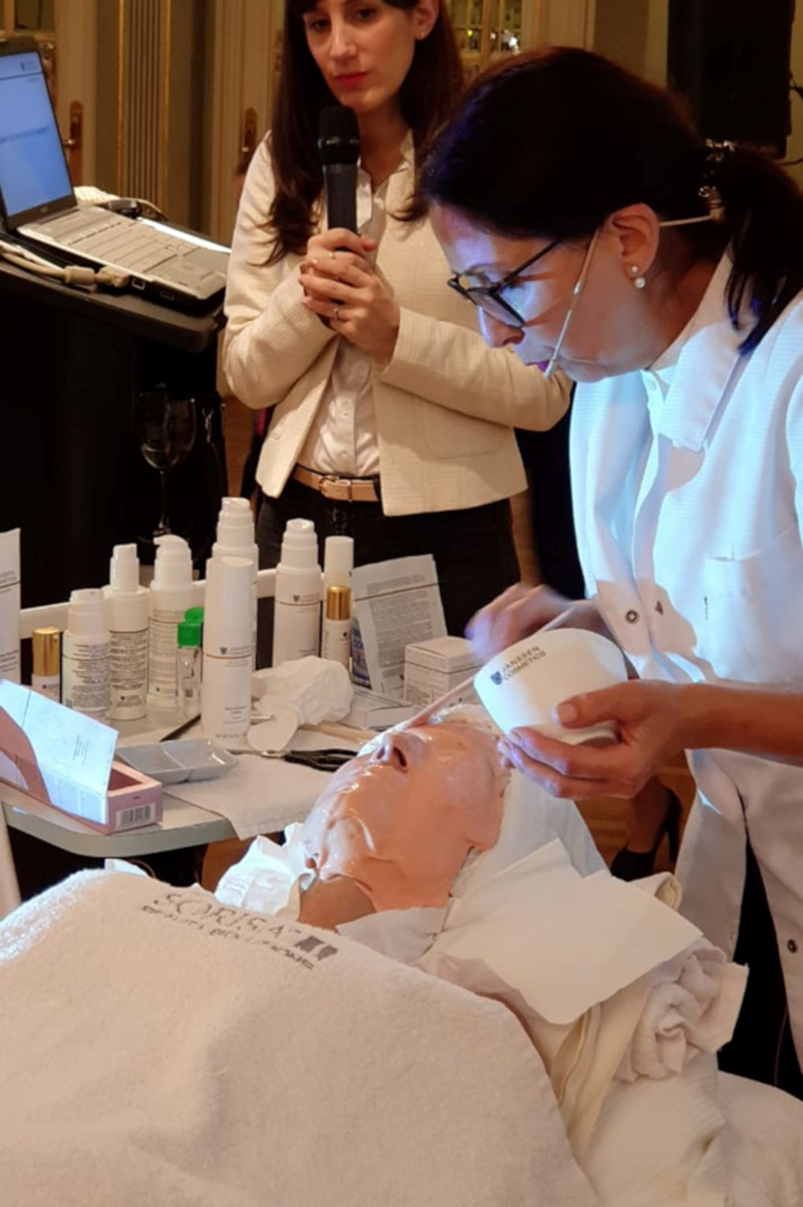 Renate Beimel demonstrating application of a peel-off mask in the cabin